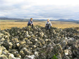 Two volunteers sit on top of somr pf the cairns within the group